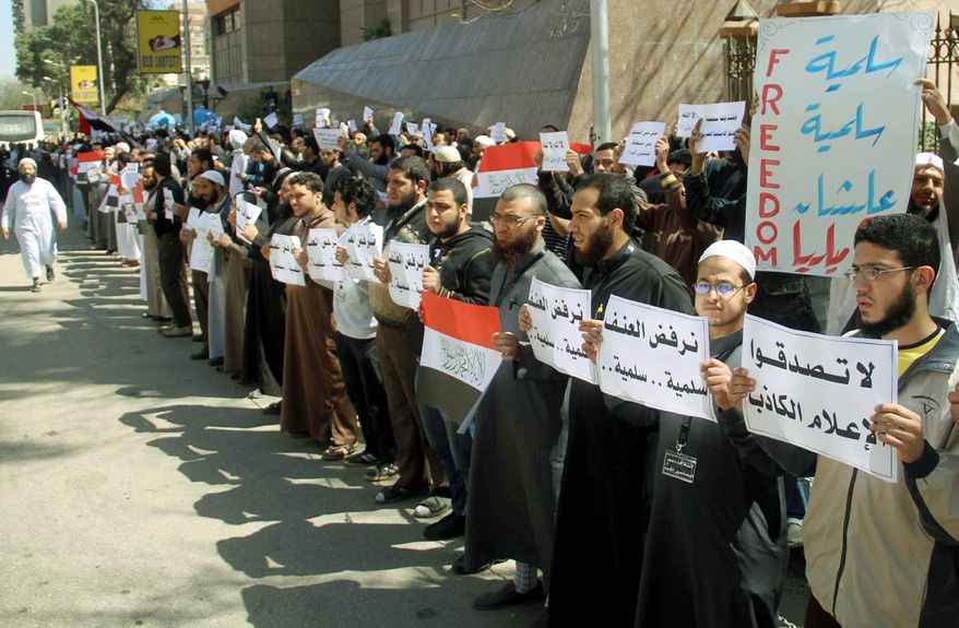 """Ultraconservative Muslims from the Salafi movement staged a protest in Cairo on Tuesday, accusing the local Christian church of abducting a Muslim convert. The protest came amid signs of increasing assertiveness by the fundamentalist movement. The signs in Arabic read: """"dont believe false media"""" and """"we reject the aggression."""" (Associated Press)"""