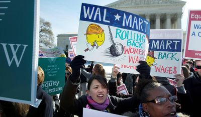 RETAIL POLITICS: Eva Yung, of Alexandria, joins other protesters at the Supreme Court on Tuesday as justices heard arguments as to whether a group of female plaintiffs can bring a class-action discrimination suit against Wal-Mart, the nation's largest private employer. (Rod Lamkey Jr./The Washington Times)