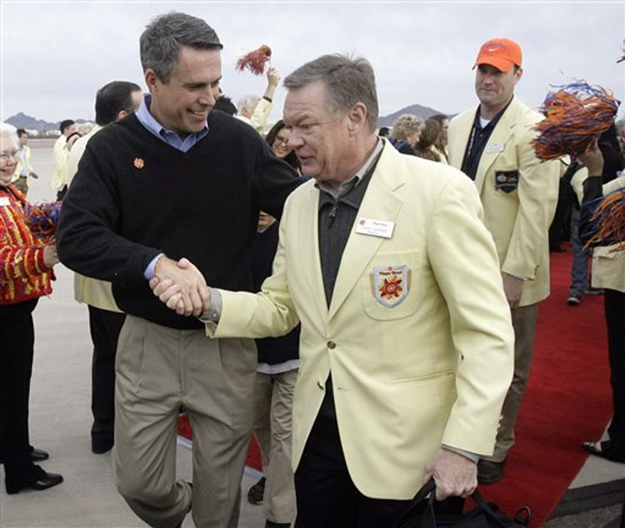 "FILE - In this Dec. 28, 2009 file photo, Boise State coach Chris Petersen, left, is greeted by Fiesta Bowl president John Junker, right, after Petersen disembarked off a charter flight at Sky Harbor International Airport in Phoenix. The Fiesta Bowl has fired its longtime CEO John Junker after a scathing internal report found ""an apparent scheme"" to reimburse employees for political contributions. (AP Photo/Paul Connors, File)"