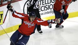 Washington Capitals left wing Alex Ovechkin, left, of Russia, reacts after scoring during the third period of an NHL hockey game against the Caroina Hurricanes at the Verizon Center in Washington, on Friday, March 11, 2011. Washington center Marcus Johansson (90) looks on. (AP Photo/Jacquelyn Martin)