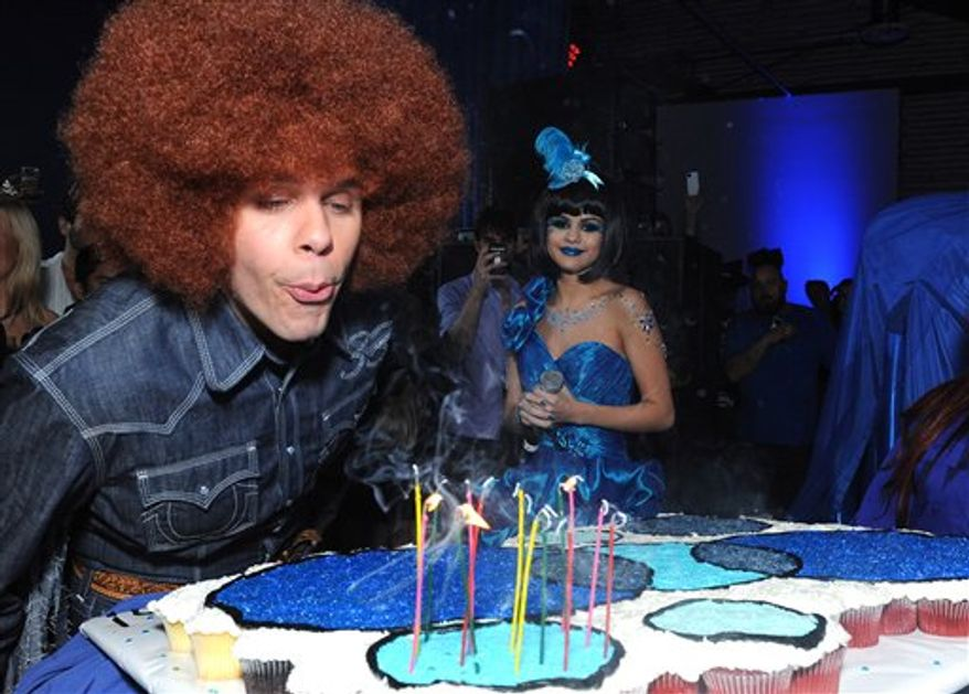 In this image provided by Perez Hilton,   Perez Hilton blows out the candles on his birthday cake during his Blue Ball birthday celebration Saturday March 26, 2011, in the Hollywood section of Los Angeles. In background looking on is Selena Gomez. (AP Photo/Katy Winn - Perez Hilton)