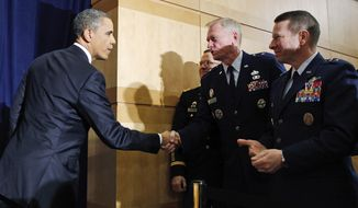 President Obama shakes hands with military officers after he spoke about Libya at the National Defense University in Washington on Monday, March 28, 2011. (AP Photo/Charles Dharapak)