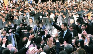 "The Syrian official news agency SANA released this photo of President Bashar Assad surrounded by supporters after a speech Wednesday in Damascus. ""If a battle is imposed on us today, we welcome it,"" he said. (SANA via Associated Press)"