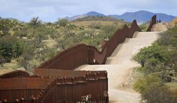 ** FILE ** A Customs and Border Protection agent patrols by car along the U.S.-Mexico border in Nogales, Ariz., in April 2010. (Associated Press)