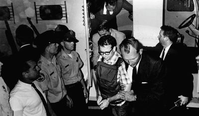 Authorities escort James Earl Ray to the Shelby County Jail in Memphis, Tenn., following his arrest two months after the assassination of Martin Luther King Jr. Ray was sentenced to prison in the civil rights leader's death and died in 1998. Then-County Sheriff Bill Morris had photos of Ray taken to document that he wasn't mistreated. (Associated Press/Shelby County Register's Office)