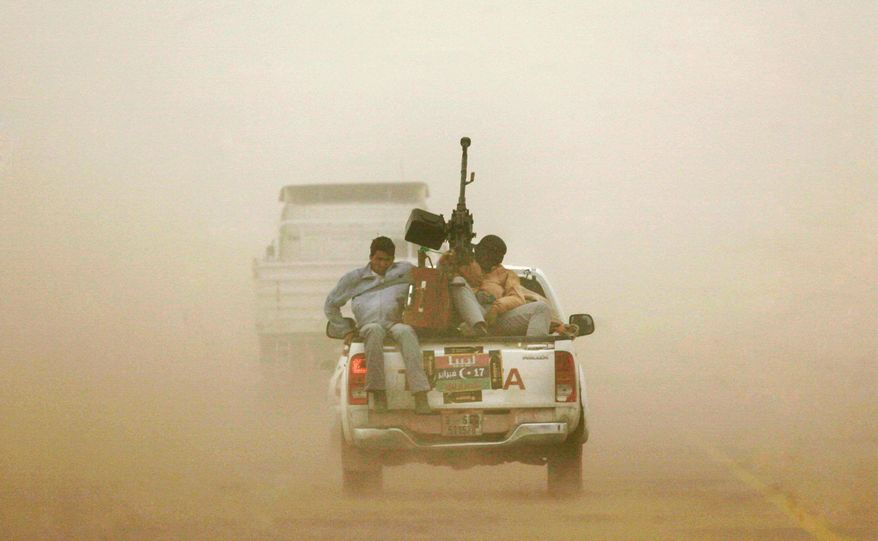 Libyan rebels riding in the back of an armed pickup truck brave a sandstorm on the main road heading to Benghazi while leaving the eastern town of Ajdabiya, Libya, on Wednesday. (Associated Press)