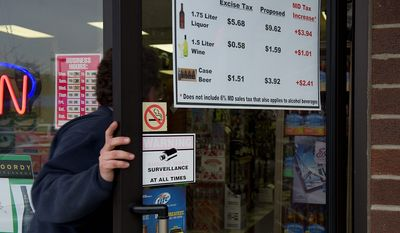 A customer enters the PM Wine & Spirits store in Pasadena, Md. on Wednesday. The store has posted a sign on its front door letting customers know that a proposed bill would add more taxes to all liquor sales in the state. (Barbara L. Salisbury/The Washington Times)