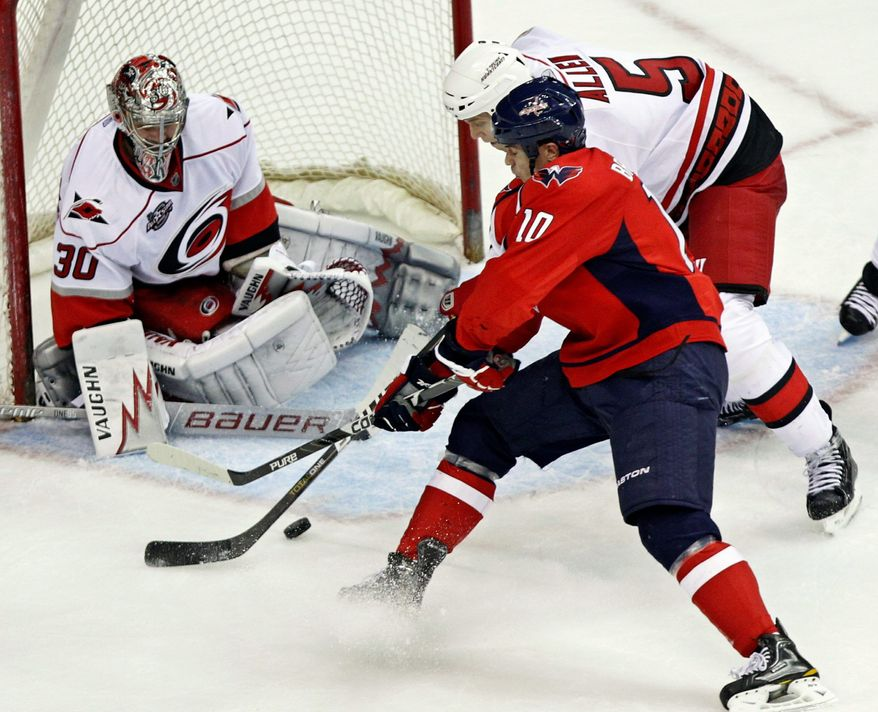 Carolina Hurricanes goalie Cam Ward (30) deflects a shot by Washington Capitals' Matt Bradley (10) while Hurricanes' Bryan Allen (5) defends during a game in Washington on Tuesday. The Hurricanes won 3-2 in a shootout. The Capitals are working to improve in power-play situations. (Associated Press)