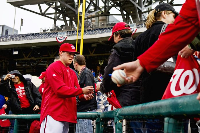 Nationals pitcher Drew Storen signs autographs at an open practice during NatsFest at Nationals Park on Wednesday. The team's seventh season in Washington opens Thursday against Atlanta. (Drew Angerer/The Washington Times)
