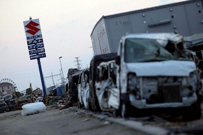 The aftermath of Japan's devastation is on display at a Suzuki company lot, where ravaged vehicles are lined up. The nation has signaled it will finance the recovery by issuing bonds. (Associated Press)