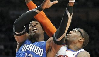Orlando Magic center Dwight Howard, left, attempts to put up a shot as New York Knicks' Amar'e Stoudemire defends during the fourth quarter of an NBA basketball game Monday, March 28, 2011 at Madison Square Garden in New York. The Knicks won 113-106 in overtime.  (AP Photo/Bill Kostroun)