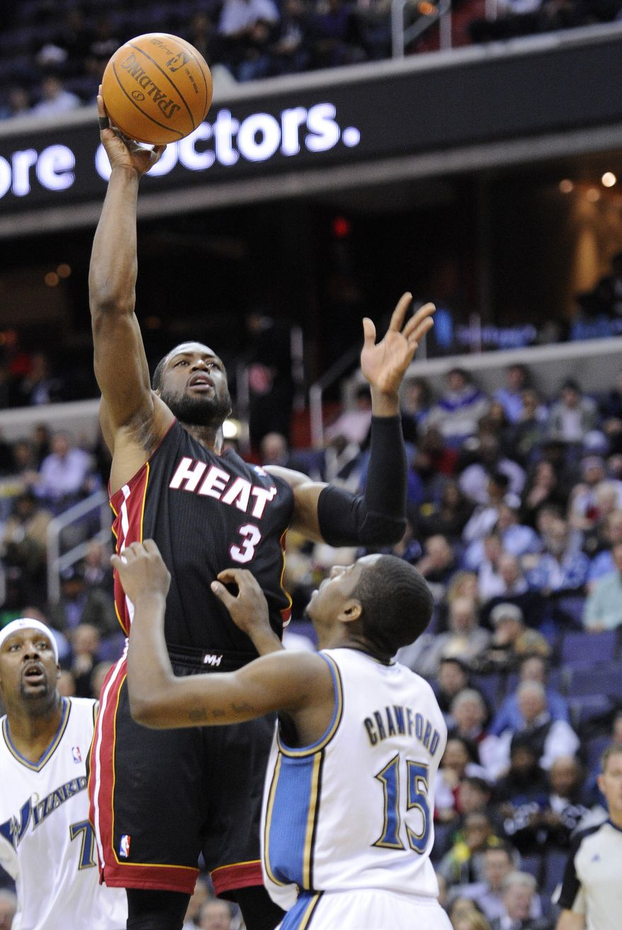 Miami Heat guard Dwyane Wade (3) goes to the basket against Washington Wizards guard Jordan Crawford (15) during the first half of an NBA basketball game, Wednesday, March 30, 2011, in Washington. (AP Photo/Nick Wass)