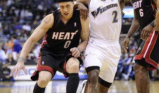 Miami Heat point guard Mike Bibby (0) dribbles against Washington Wizards point guard John Wall (2) during the first half of an NBA basketball game, Wednesday, March 30, 2011, in Washington. (AP Photo/Nick Wass)