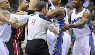 Washington Wizards point guard John Wall, second from right, scuffles with Miami Heat center Zydrunas Ilgauskas, center, during the first half of an NBA basketball game, Wednesday, March 30, 2011, in Washington. Both players were ejected from the game. (AP Photo/Nick Wass)