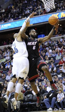 Miami Heat forward LeBron James, right, goes to the basket against Washington Wizards forward Maurice Evans, left, during the first half of an NBA basketball game, Wednesday, March 30, 2011, in Washington. (AP Photo/Nick Wass)
