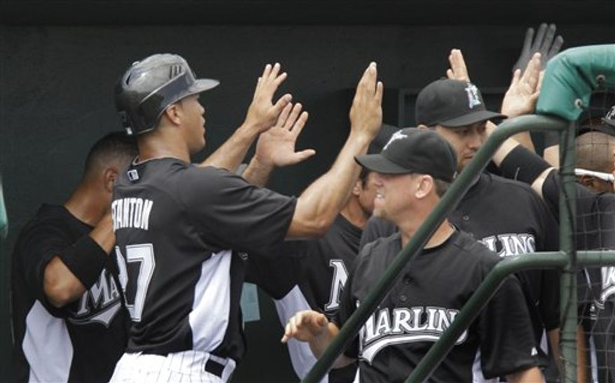 Florida Marlins' Mike Stanton (27) high fives his teammates after scoring during the first inning of a spring training baseball game against the New York Mets, Friday, March 25, 2011 in Jupiter, Fla. (AP Photo/Carlos Osorio)
