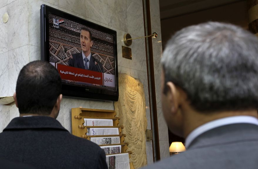 """Syrians watch President Bashar Assad on television as he addresses parliament in Damascus, Syria, on Wednesday, March 30, 2011. Mr. Assad, giving his first speech to the nation since anti-government protests erupted in this tightly controlled Arab state, blamed """"conspirators"""" for trying to destroy the country. The speech was seen as a crucial test for Mr. Assad's leadership and one that may determine Syria's future. (AP Photo/Hussein Malla)"""