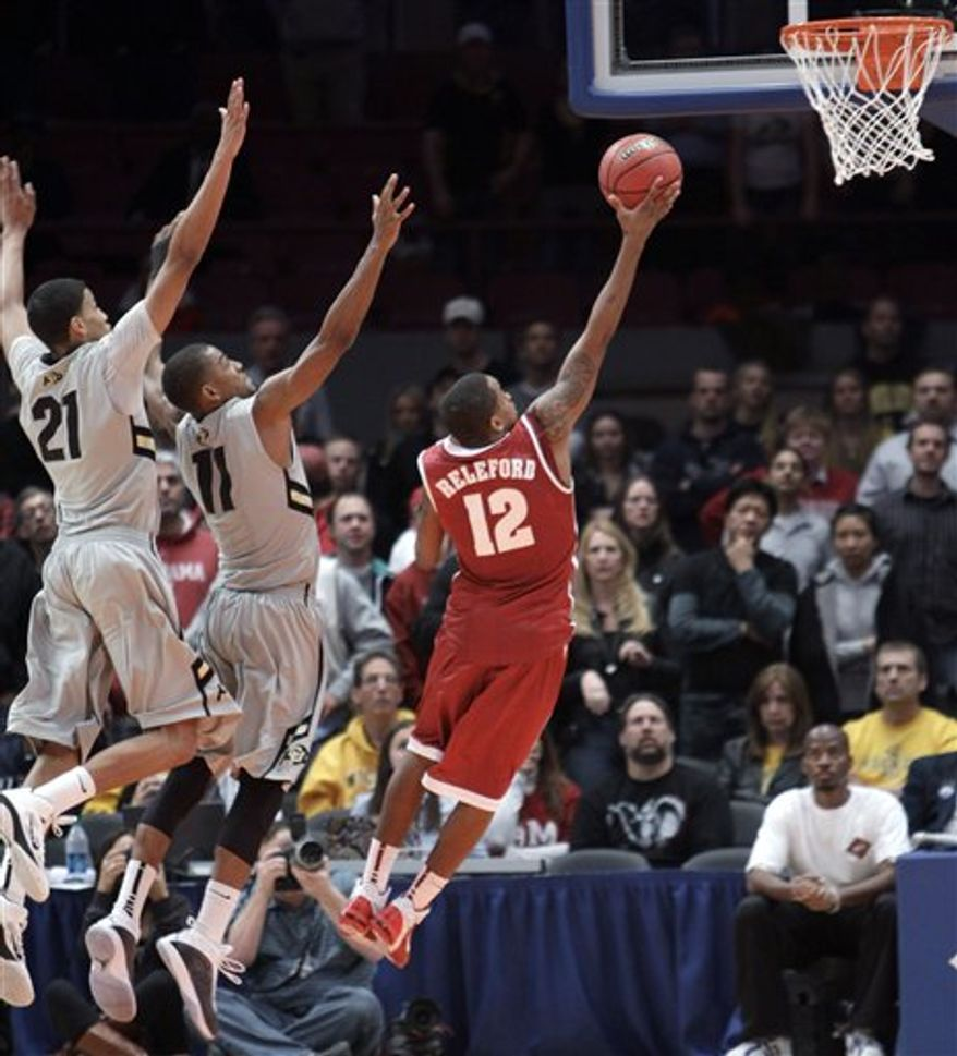 Alabama's Trevor Releford (12) goes up against Colorado's Andre Roberson (21) and Cory Higgins to score the winning goal in the final seconds of a semifinal in the NIT college basketball tournament, Tuesday, March 29, 2011, at Madison Square Garden in New York. Alabama defeated Colorado 62-61. (AP Photo/Mary Altaffer)