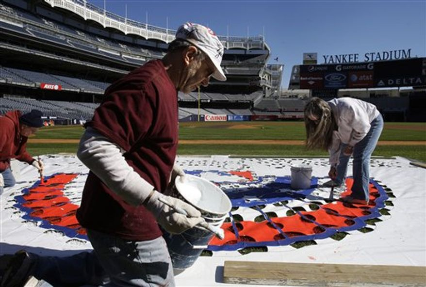 Kevin Healy, center, David Hollenbach, left, and Cecilia Kunath paint a logo on the field at Yankee stadium in preparation for opening day,  Tuesday, March 29, 2011, in New York. (AP Photo/Frank Franklin II)