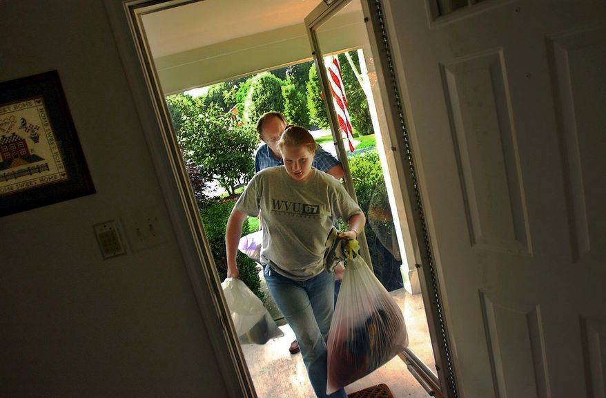 **FILE** West Virginia University student Jennifer Greenwell (front) and her father, Ron, carry her belongings into her parents' Springfield, Va., home as she returns on June 28, 2002. (Rod Lamkey Jr./The Washington Times)