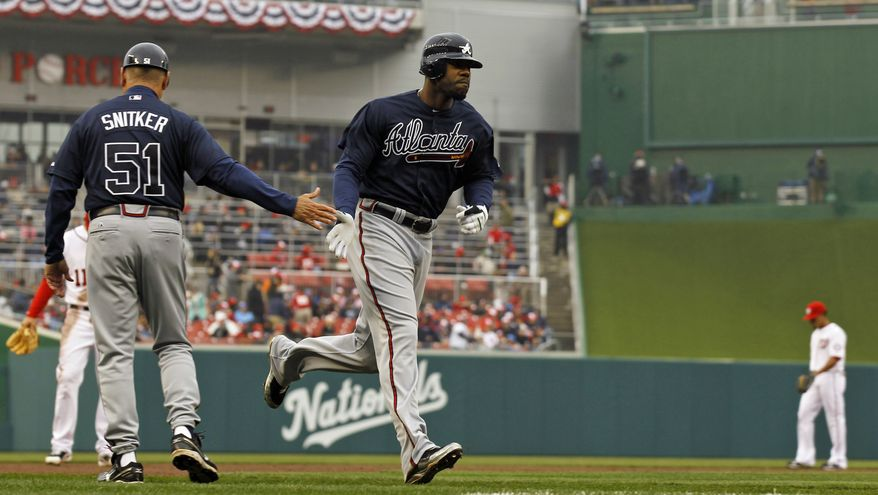 Atlanta Braves' Jason Heyward is congratulated by third base coach Brian Snitker after a solo home run in the second inning of the Braves' 2-0 victory over the Washington Nationals on Thursday in Washington. (Associated Press)