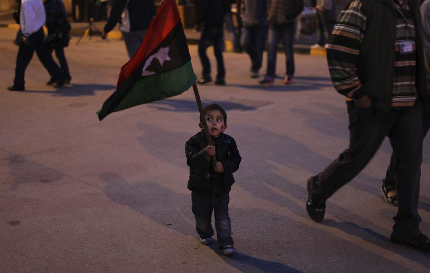 A Libyan child walks with a Libyan pre-Gadhafi flag during an evening demonstration in Benghazi, Libya, on Wednesday, March 30, 2011. Rebels retreated Wednesday from the key Libyan oil port of Ras Lanouf along the coastal road leading to the capital Tripoli after they came under heavy shelling from ground forces loyal to leader Moammar Gadhafi. (AP Photo/Altaf Qadri)