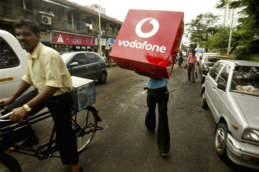 FILE -  In this Sept. 20, 2007 file photo, an Indian worker carries a Vodafone sign to erect it on a street lamp post in Mumbai, India. Vodafone said Thursday, March 31, 2011 it it paying $5 billion cash to buy out the Essar Group's stake in their Indian joint venture. The buyout of Essar's 33 percent stake has been long expected and brings to an end what by many accounts has been an increasingly sour relationship between the partners. (AP Photo/Gautam Singh, File)