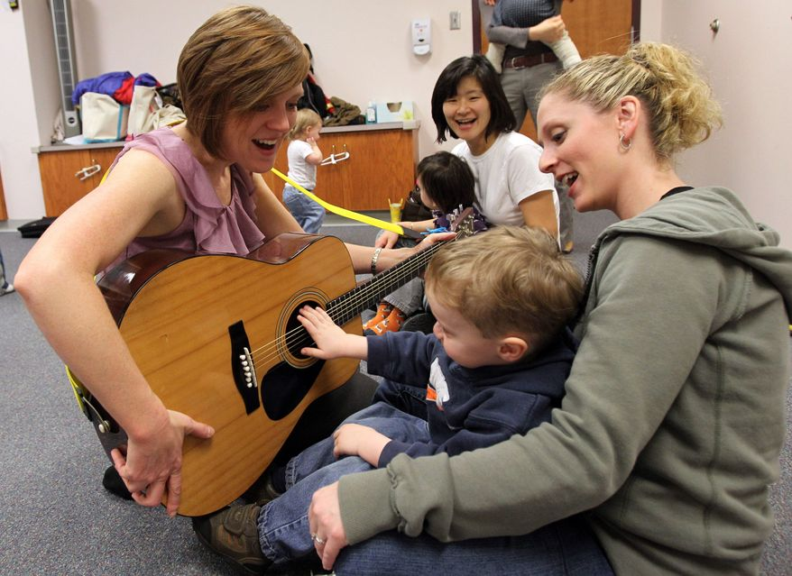 This Monday, March 7, 2011, photo shows Joni Pappas left, as she plays guitar with Jackson Brooks, 2, and his mother, Lauren Brooks, both of Huntington, during Pappas toddler music class at Marshall University in Huntington, W.Va. (AP Photo/The Herald Dispatch, Lori Wolf)