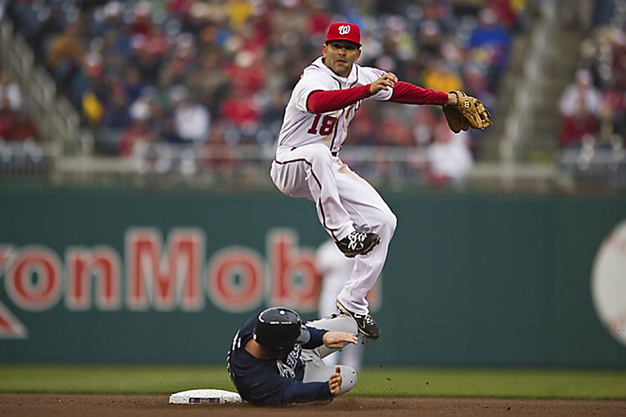 Nationals second baseman Danny Espinosa forces out Brian McCann as he tries to turn a double play on a ball hit by Dan Uggla during the 7th inning of the opening day game against the Atlanta Braves at Nationals Park, in Washington, D.C., Thursday, March 31, 2011. (Drew Angerer/The Washington Times)