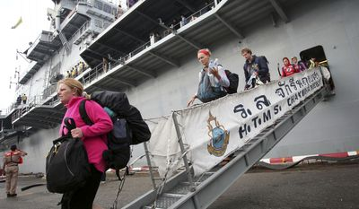Foreign tourists arrive at Sattahip Naval Base in Chonburi province, Thailand, after being transported by a Royal Thai Navy ship Thursday, March 31, 2011. Thailand's navy has used helicopters and even an aircraft carrier to rescue more than 800 tourists stranded by heavy rains on the country's picturesque southern islands. (AP Photo)