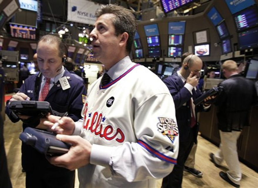 Trader William Sachs, in a Philadelphia Phillies jersey, in observance of Major League Baseball's opening day, works on the floor of the New York Stock Exchange Thursday, March 31, 2011. (AP Photo/Richard Drew)
