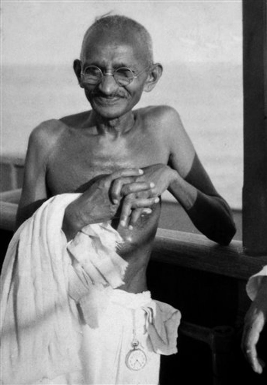 FILE - In this undated file photo, Mahatma Gandhi smiles aboard the S.S. Rajputana en route to the Second Round Table Conference on Dominion Status for India, (September - December 1931) in London. A state in western India banned Pulitzer-Prize winning author Joseph Lelyveld's new book about Mahatma Gandhi on Wednesday, March 30, 2011, after reviews saying it hints that the father of India's independence had a homosexual relationship. (AP Photo/James A. Mills, File)