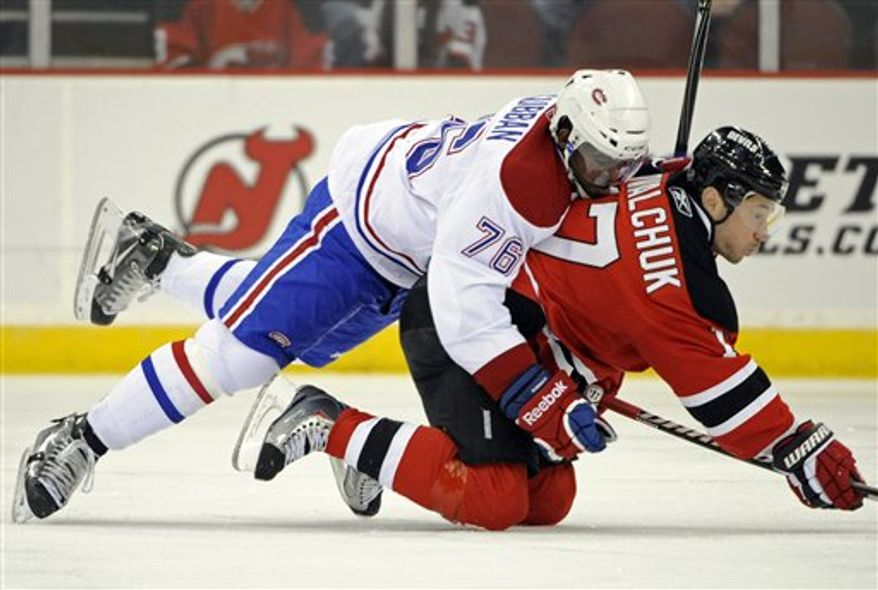 New Jersey Devils' David Steckel, right, falls over Montreal Canadiens' David Deshamais during the second period of an NHL hockey game on Saturday, April 2, 2011, in Newark, N.J. (AP Photo/Bill Kostroun)
