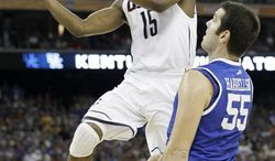 Connecticut's Kemba Walker shoots as Kentucky's DeAndre Liggins looks on during the first half of a men's NCAA Final Four semifinal college basketball game Saturday, April 2, 2011, in Houston. (AP Photo/David J. Phillip)
