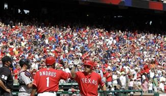Texas Rangers' Nelson Cruz, front, trots home after his solo home run off Boston Red Sox's Clay Buchholz, back, in the seventh inning of an MLB baseball game on Sunday, April 3, 2011, in Arlington, Texas. (AP Photo/Tony Gutierrez)