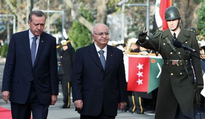 Turkish Prime Minister Recep Tayyip Erdogan (left) walks with Syrian counterpart, Naji al-Otari. He has urged Libyan dictator Moammar Gadhafi to step down. (Associated Press)