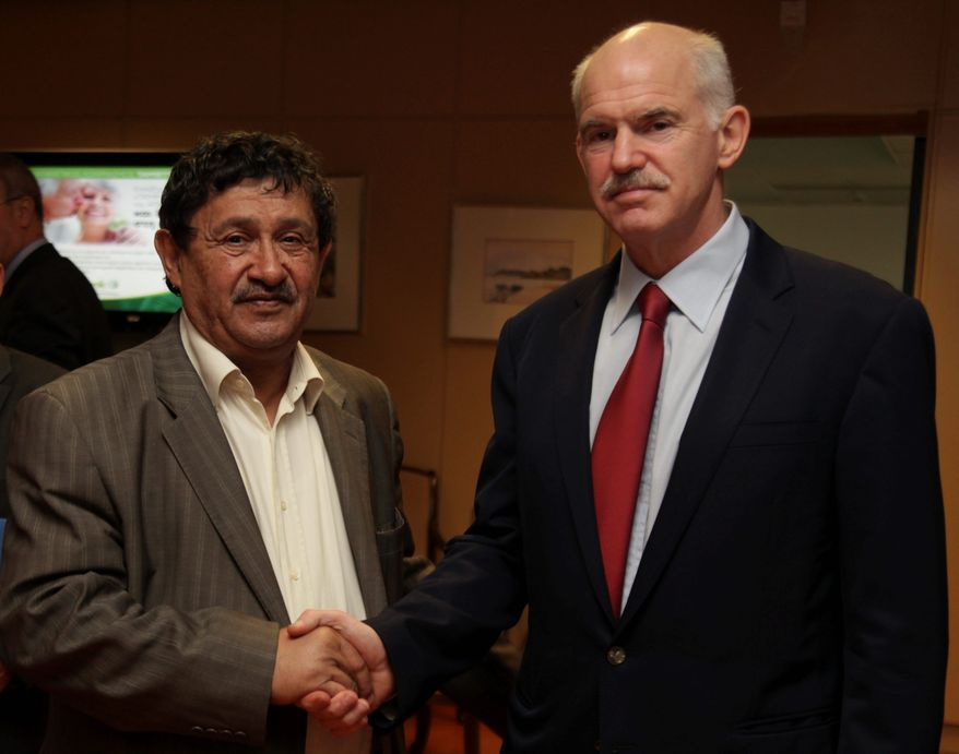Greek Prime Minister George Papandreou (right) shakes hands with Libyan Deputy Foreign Minister Abdel Ati al-Obeidi on Sunday. Mr. Papandreou has been consulting with other nations on diplomatic initiatives to end the war in Libya. (Associated Press)