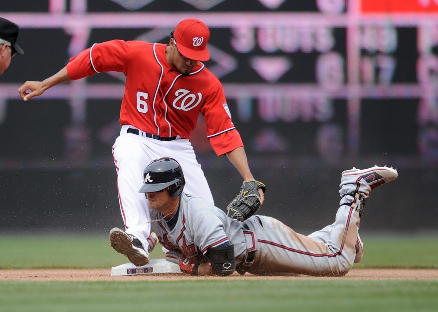 Nationals shortstop Ian Desmond (6) applies a late tag as Atlanta's Martin Prado slides into second base for a double during the seventh inning of the Braves' 11-2 win Sunday. The Nationals dropped to 1-2 with the loss. (Associated Press)