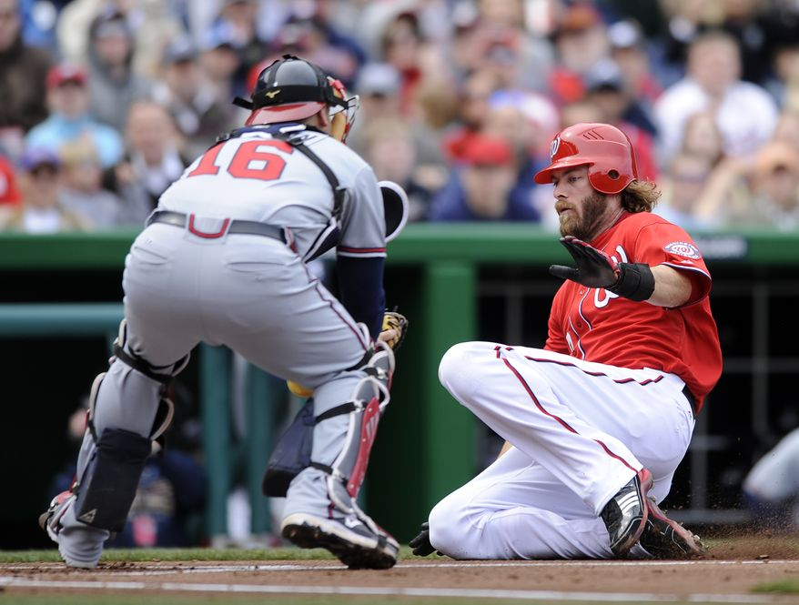Washington Nationals' Jayson Werth, right, slides home to score against Atlanta Braves catcher Brian McCann (16) during the first inning of a baseball game on Sunday, April 3, 2011, in Washington. (AP Photo/Nick Wass)