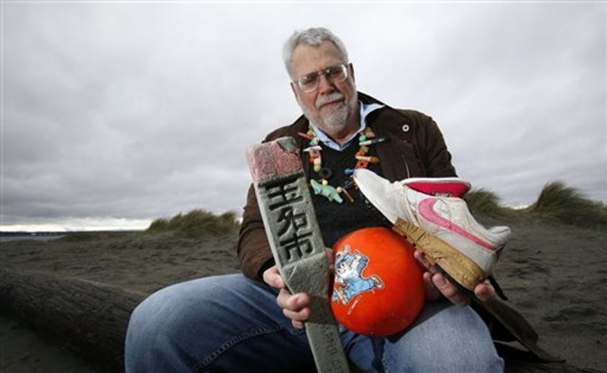 Oceanographer Curt Ebbesmeyer holds a necklace made of ocean flotsam as he talks about how debris from Japan will wash ashore in Washington, as he sits at a Puget Sound beach Wednesday, March 30, 2011, in Seattle. Ebbesmeyer, who has traced Nike sneakers, rubber bath toys and hockey gloves spilled from Asian shipping containers over the decades, expects the first items of flotsam from Japan's tsunamis and earthquake to hit West Coast beaches in a year. He says derelict fishing vessels may show up first, while other items like pieces from wooden homes and rubber survey stakes may take two to three years. (AP Photo/Elaine Thompson)