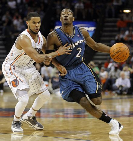 Washington Wizards' John Wall, right, is fouled as he drives past Charlotte Bobcats' D.J. Augustin in the second half of the Wizards' 97-91 win in an NBA basketball game in Charlotte, N.C., Sunday, April 3, 2011. (AP Photo/Chuck Burton)