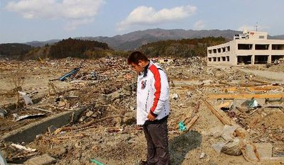 Naoki Suzuki, a truck driver, stands near the site of his home in downtown Rikuzen-Takata where his wife, Kazue, tried to ride out the tsunami as it rose above a nearby three-story apartment complex and post office. (Christopher Johnson/Special to The Washington Times)
