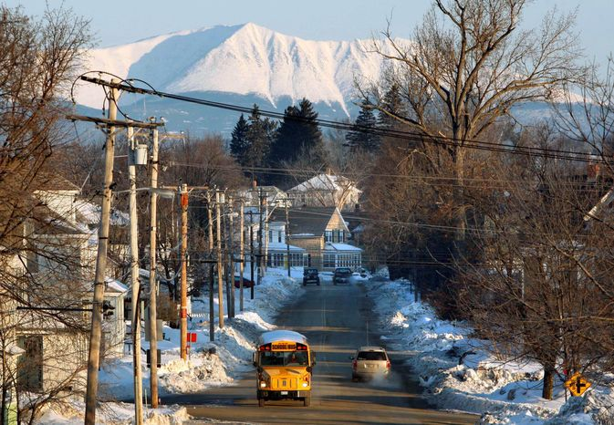 With Mount Katahdin rising in the background, a school bus makes its rounds in Millinocket, Maine, in 2011. The town's public high school is touting its natural resources in an effort to offset a dwindling population by recruiting foreign students. (Associated Press)