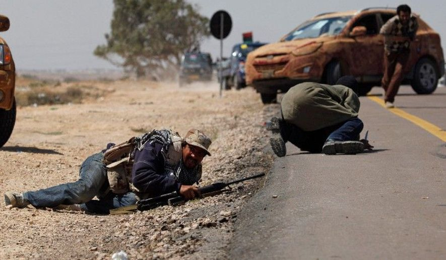 UNDER FIRE: Two Libyan rebels duck as others take cover when attacked by pro-Gadhafi forces along the front line on the outskirts of Brega, Libya, on Monday. Meanwhile, a government envoy is in Europe for talks about ending the fighting. (Associated Press)
