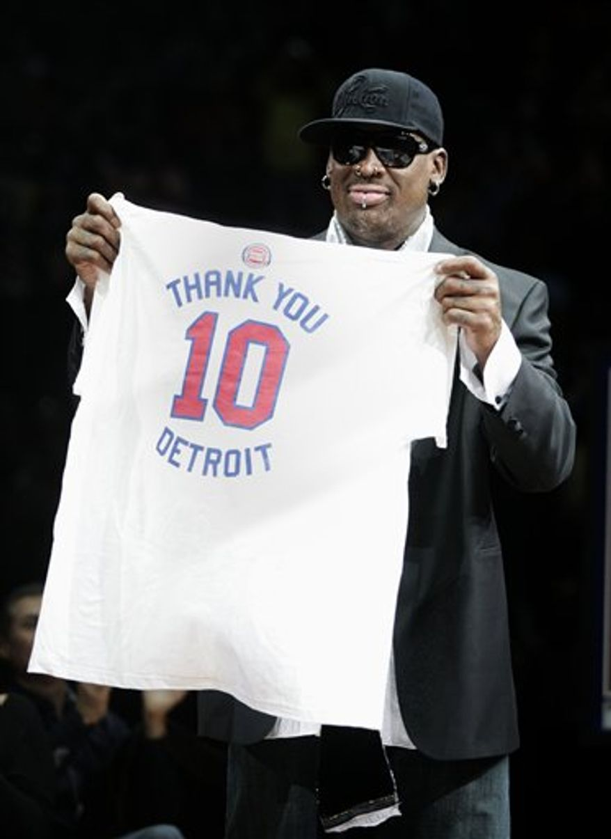 Former Detroit Piston Dennis Rodman holds up a t-short with his number 10 to thank the fans during a ceremony to retire his jersey at an NBA basketball game against the Chicago Bulls Friday, April 1, 2011, in Auburn Hills, Mich. (AP Photo/Duane Burleson)