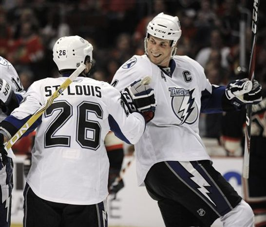 Tampa Bay Lightning's Vincent Lecavalier right, celebrates with teammate Martin St. Louis after scoring against the Chicago Blackhawks in the first period during an NHL hockey game in Chicago, Sunday, April 3, 2011. (AP Photo/Paul Beaty)