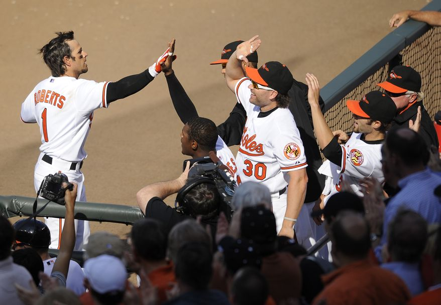 Baltimore Orioles' Brian Roberts (1) celebrates his three-run home run during the fifth inning of a baseball game against the Detroit Tigers, Monday, April 4, 2011, in Baltimore. Also seen is Baltimore's Luke Scott (30) .(AP Photo/Nick Wass)
