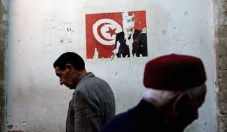 Tunisian men pass a poster with the face of former Tunisian President Zine El Abidine Ben Ali torn away in downtown Sfax, Tunisia. Tunisians have embarked on a difficult transition to democracy since overthrowing their autocratic ruler of 23 years nearly three months ago. They cherish their new freedom, but also worry about the future. (Associated Press)
