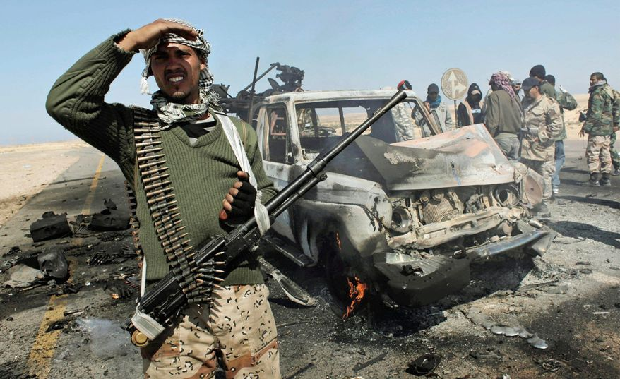 One Libyan rebel keeps a lookout as others inspect two destroyed vehicles of pro-Gadhafi forces that rebels claim were targeted by a NATO strike Tuesday on the front line near Brega. Libya's rebel forces are looking more effective on the front and recovering some territory lost to Moammar Gadhafi's army. (Associated Press)