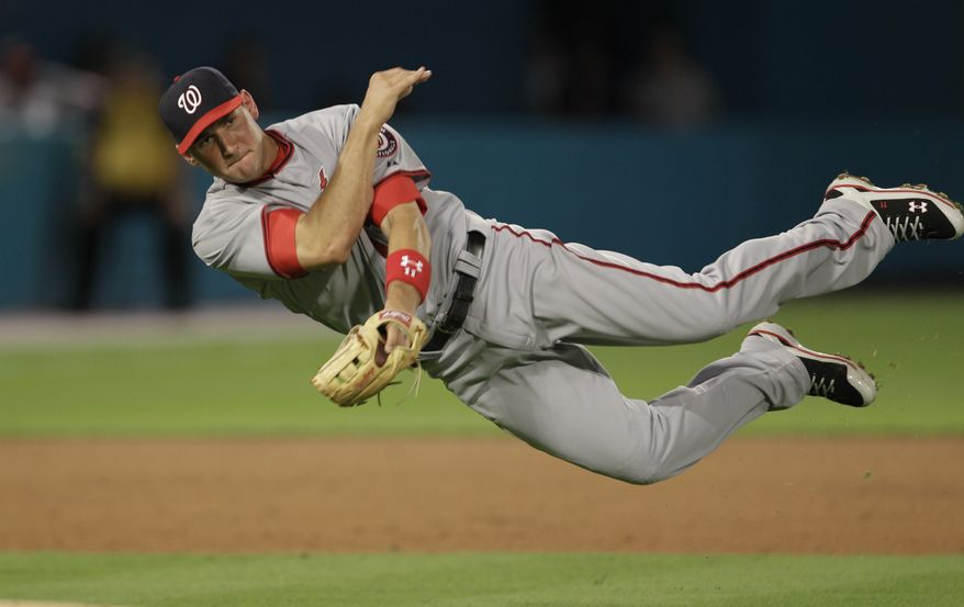 Washington Nationals Ryan Zimmerman is unable to throw Florida Marlins runner Omar Infante out at first during the third inning of a baseball game in Miami, Tuesday, April 5, 2011. (AP Photo/J Pat Carter)